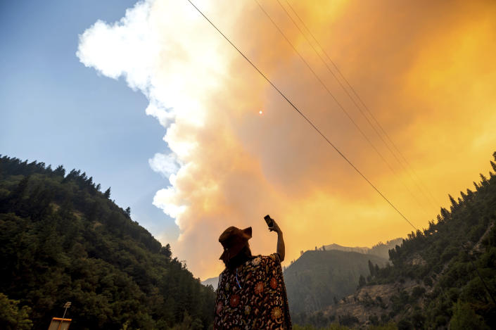 Jessica Bell takes a video as the Dixie Fire burns along Highway 70 in Plumas National Forest, Calif., on Friday, July 16, 2021. (AP Photo/Noah Berger)