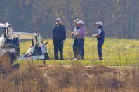 President Donald Trump, center standing, as he participates in a round of golf at the Trump National Golf Course on Saturday, Nov. 7, 2020, in Sterling, Va. (AP Photo/Patrick Semansky)