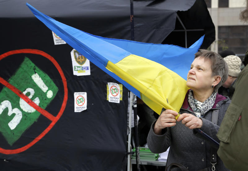 A woman holds an Ukrainian flag standing next to a tent of opponents of comedian and presidential candidate Volodymyr Zelenskiy in downtown Kiev, Ukraine, Wednesday, April 17, 2019. The second round of presidential vote in Ukraine will take place on April 21. (AP Photo/Sergei Grits)