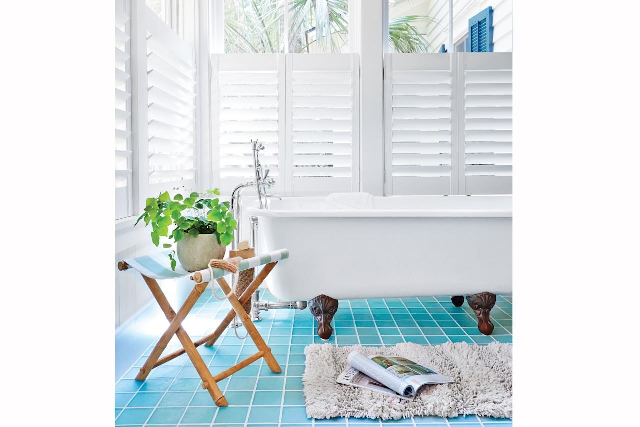 <p>Transform your bath into an at-home spa by emulating nature. The blue tiles pictured here bring to mind the undulating waters of the sea, and the palms visible through the plantation shutters truly bring the outside in. </p> <p>Idea Spotlight: A folding luggage rack is a perfect tub-side spot for holding towels, books, and small potted plants when not in use.</p>