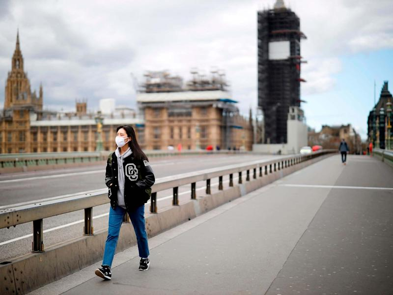 A woman wearing a face mask as a precautionary measure against Covid-19 walks across a deserted Westminster Bridge in London: Tolga Akmen/AFP/Getty