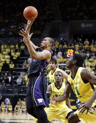 Washington's Andrew Andrews, left, drives to the basket past Oregon's Johnathan Loyd, center, and Damyean Dotson, right, during the first half an NCAA college basketball game in Eugene, Ore., Saturday, Jan 26, 2013. (AP Photo/Chris Pietsch)