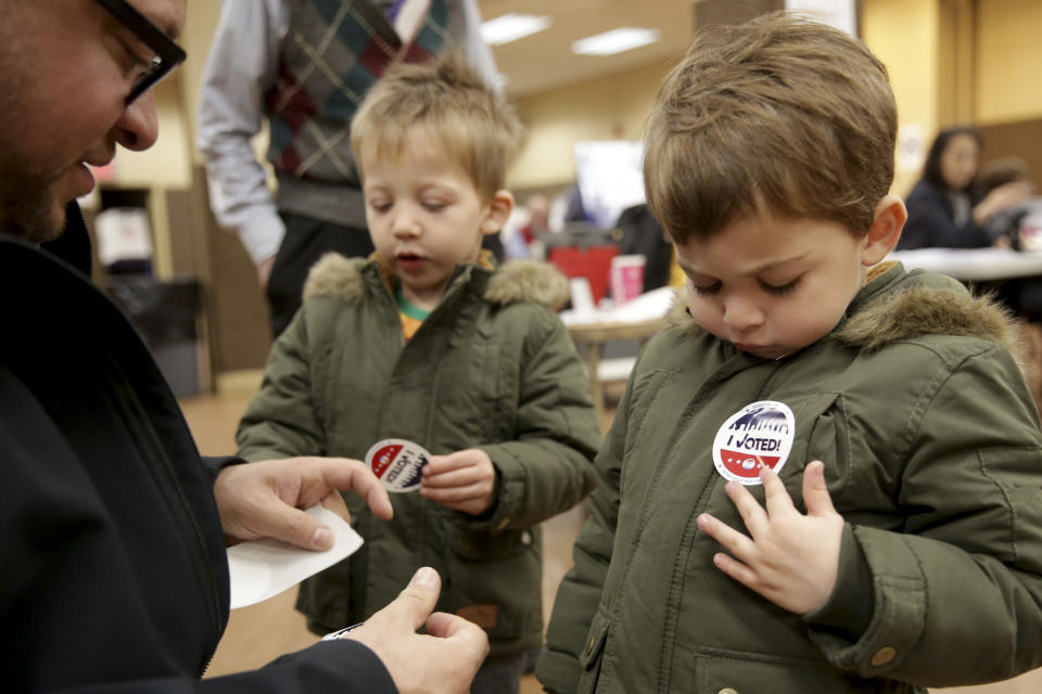 """Twins Amir, right, and Milo Klatzkin, 3, put on their """"I Voted"""" stickers after their father Barry Klatzkin, left, voted at a polling site in New York, Tuesday, Nov. 5, 2019. New York's first election with early voting is reaching its conclusion as people across the state cast ballots in county and municipal races. With no federal or statewide contests on the ballot Tuesday, turnout is expected to be low, but this year's contests are serving as a rehearsal for next year's blockbuster presidential race. (AP Photo/Seth Wenig)"""