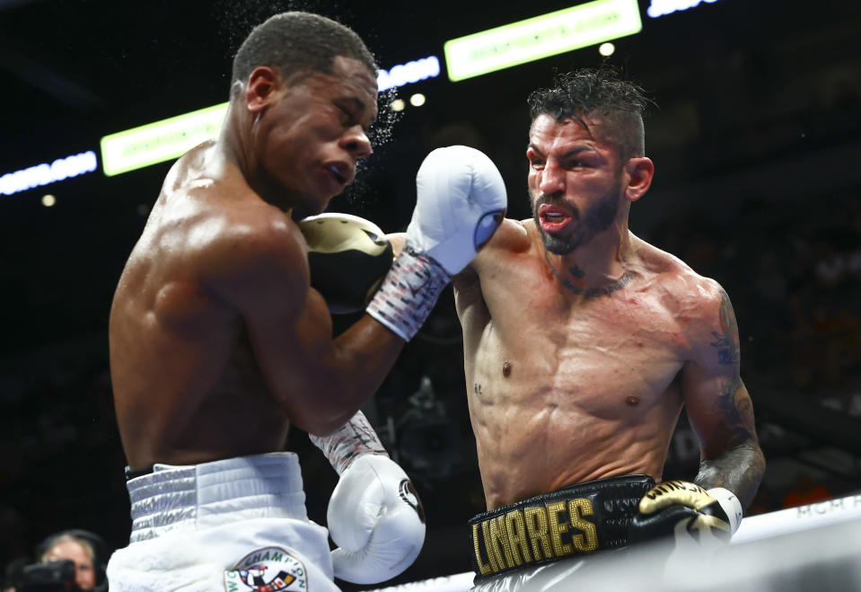 Jorge Linares, right, punches Devin Haney during the WBC lightweight title boxing match Saturday, May 29, 2021, in Las Vegas. (AP Photo/Chase Stevens)