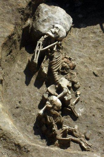This handout photo, provided by the Bulgarian National Institute of Archeology, shows the remains of a man and two children in the necropolis of a small settlement made of two-story houses near the town of Provadia in eastern Bulgaria. Archeologists have uncovered the remains of what could be the oldest prehistoric city in Europe founded around a salt mine and dating back to the 5th millennium BC