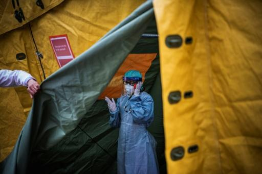 A medical staffer at Sophiahemmet hospital talks on a cell phone inside a tent for testing and receiving potential coronavirus patients in Stockholm, Sweden