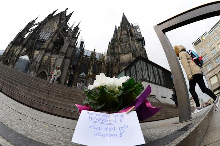 """Flowers and a letter reading """"One doesn't beat women - not even with flowers"""" are laid down in front of Cologne's landmark cathedral, near the main railway station, on January 7, 2016 (AFP Photo/Roberto Pfeil)"""