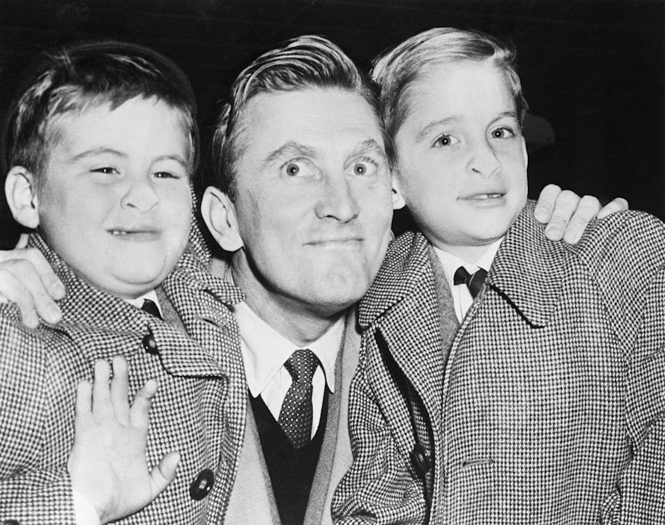 <p>Kirk smiles with his sons, Michael and Joel, at the airport in New York in 1953. The two young boys goof around for the cameras. </p>