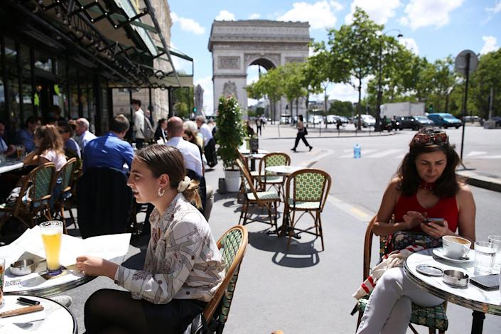 People have lunch at a restaurant near the Arc de Triomphe in Paris, France, June 18, 2020