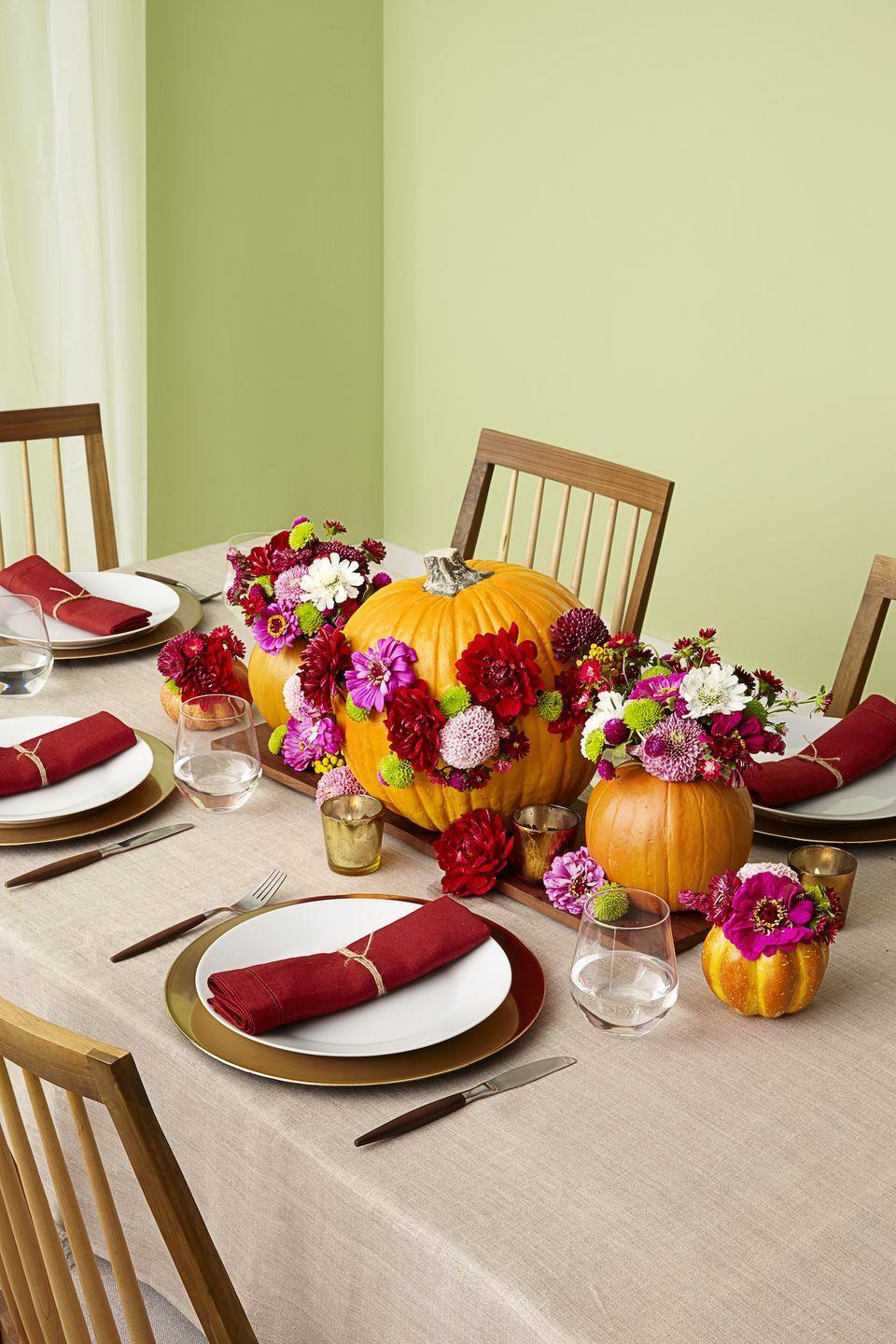 <p>Hot glue vibrant faux flowers on a bright orange pumpkin to add a wow-factor to your table. You can add smaller pumpkin vases to complete your look. </p>