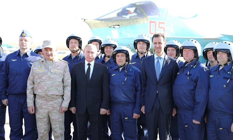 Vladimir Putin (third left) and Bashar al-Assad (third right) pose with pilots at Khmeimim airbase