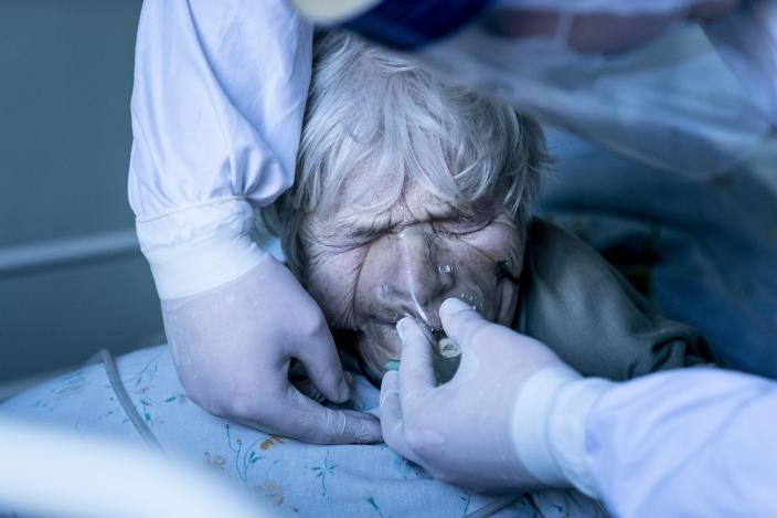 A medic wearing a special suit against coronavirus adjusts a coronavirus patient's oxygen mask at the intensive care unit at a hospital in the mining town of Selydove, 700 kilometers (420 miles) east of Kyiv, eastern Ukraine, Thursday, March 4, 2021. Ukraine received its first shipment of vaccine 500,000 AstraZeneca doses in late February. Yet, only about 19,000 people have been vaccinated since then. Ukrainians are becoming increasingly opposed to vaccination: an opinion poll this month by the Kyiv International Institute of Sociology found 60% of the country's people don't want to get vaccinated, up from 40% a month earlier. (AP Photo/Evgeniy Maloletka)