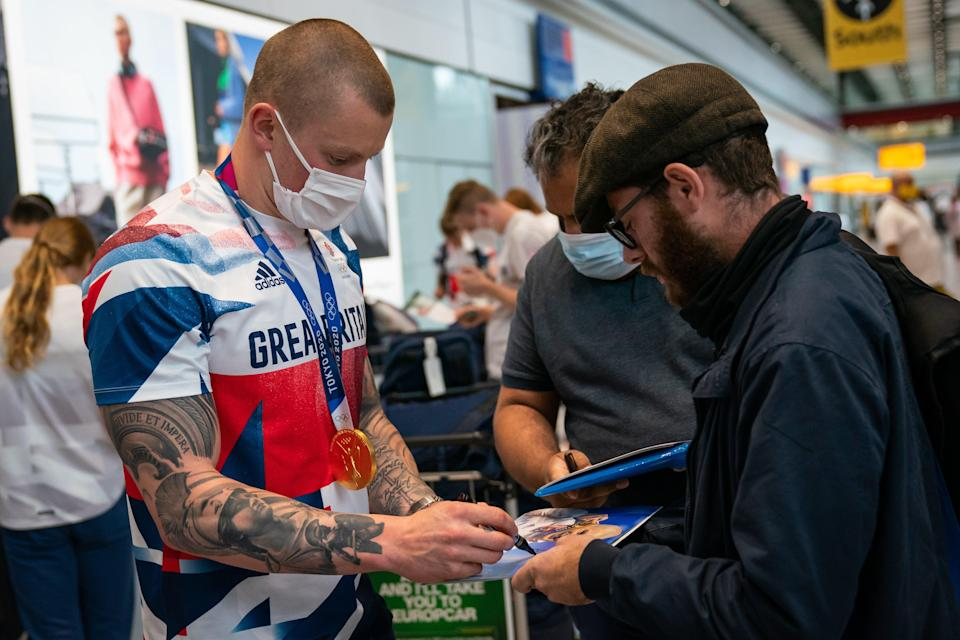 Adam Peaty sign autographs at Heathrow Airport (Aaron Chown/PA) (PA Wire)