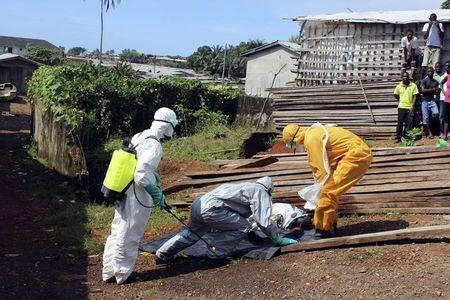 Health workers remove the body a woman who died of Ebola virus in the Aberdeen district of Freetown