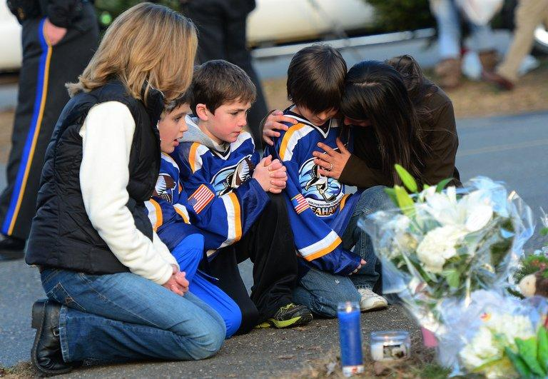 People pay tribute to the victims of an elementary school shooting in Newtown, Connecticut, on December 15, 2012