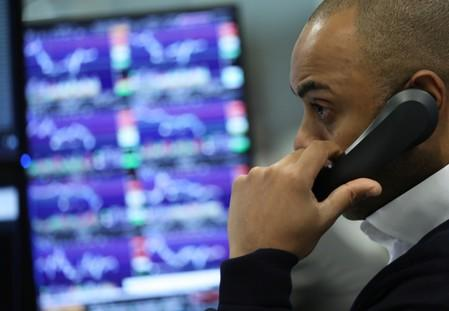 A trader works as screens show market data at CMC markets in London