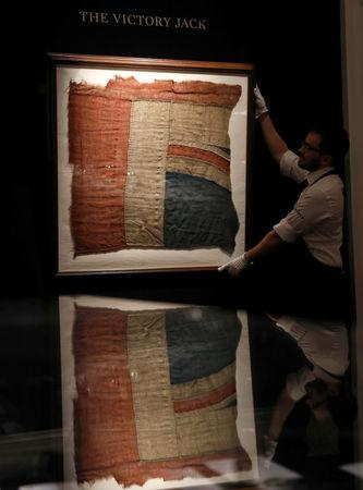 FILE PHOTO: A member of Sotheby's staff poses for a photograph with a large fragment of Lord Nelson's union flag which flew from the HMS Victory during the Battle of Trafalgar London, Britain January 11, 2018.  REUTERS/Peter Nicholls/File Photo