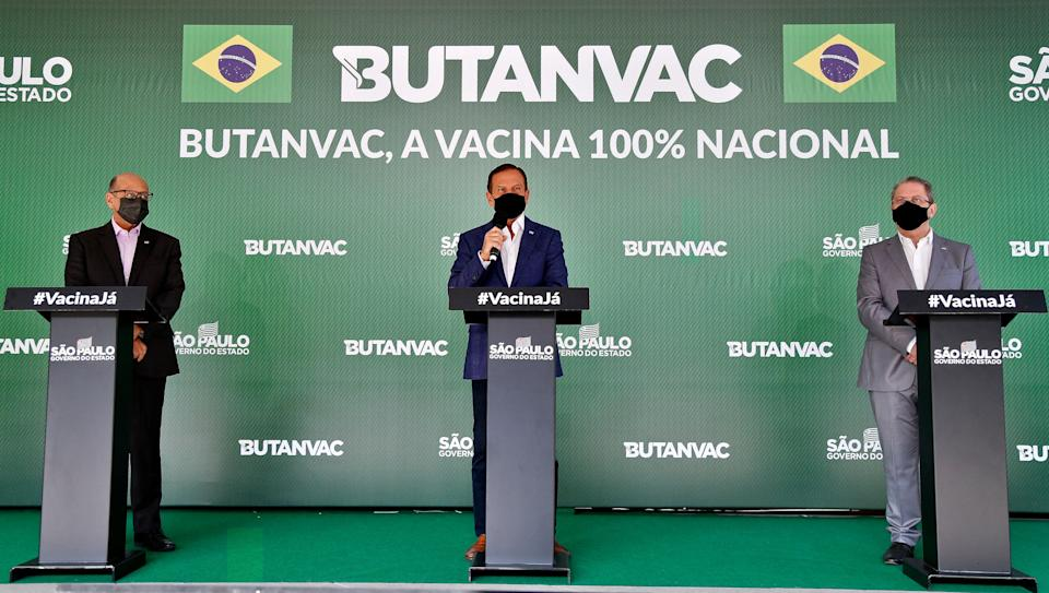 (L-R) Butantan Institute director Dimas Covas, Sao Paulo Governor Joao Doria and Sao Paulo Health Secretary Jean Gorinchteyn, present the ButanVac vaccine candidate against Covid-19, at the Butantan Institute, in Sao Paulo, Brazil, on March 26, 2021. - The Brazilian ButanVac vaccine will ask for authorization from the National Health Surveillance Agency (Anvisa) to start clinical trials of phases 1 and 2 in humans, involving 1,8 thousand volunteers. Research started on March 26, 2020 and the production goal is to start on May and to deliver 40 million doses starting on July, 2021. (Photo by Miguel SCHINCARIOL / AFP) (Photo by MIGUEL SCHINCARIOL/AFP via Getty Images)