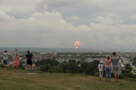People watch flame and smoke rising from the site of blasts at an ammunition depot in Krasnoyarsk region