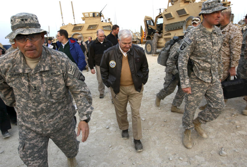 FILE - In this Dec. 7, 2010 file photo, Defense Secretary Robert Gates walks with Maj. Gen. John Campbell, left,, commanding general of the 101st Air Assault, in Kunar Province, Afghanistan. The U.S. military will start carrying out more counterterrorism missions against insurgents in eastern Afghanistan and work more closely with Pakistani forces in operations against insurgents along the porous and rugged frontier, the U.S. general commanding the region said. Maj. Gen. Campbell, commander of NATO coalition forces in eastern Afghanistan, said he has been repositioning some of his troops since last August to make them more effective in the region that borders Pakistan. The area has seen an upsurge in violence and is a main route for insurgents infiltrating into Afghanistan from safe havens in Pakistan's lawless tribal regions. (AP Photo/Win McNamee, Pool, File)