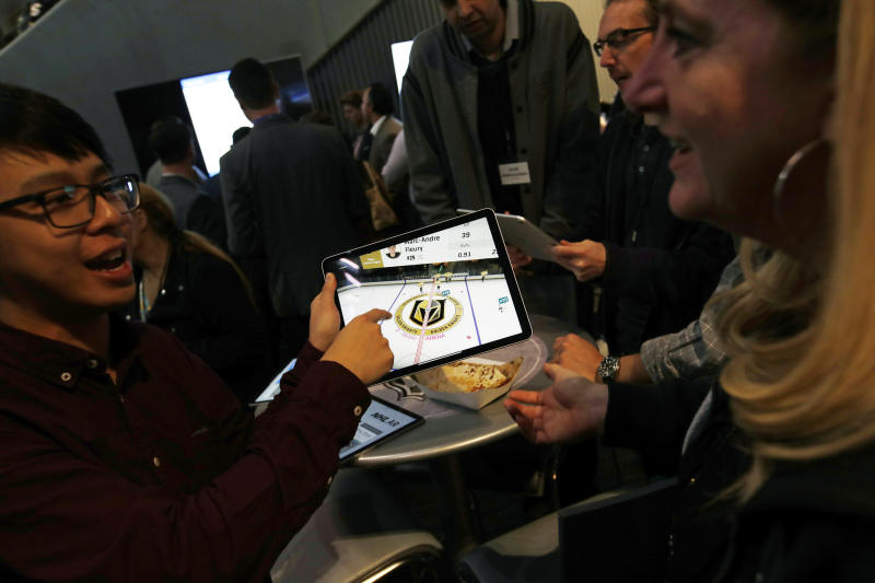 People watch real-time puck and player tracking technology on a tablet during an NHL hockey game between the Vegas Golden Knights and the San Jose Sharks in Las Vegas, Thursday, jan. 10, 2019. The NHL for the first time has tested real-time puck and player tracking in regular-season games with the aim of having it ready for the 2019-20 season. Microchips were added to players' shoulder pads and fitted inside specially designed pucks for two Vegas Golden Knights home games this week: Tuesday against the New York Rangers and Thursday against the San Jose Sharks. Antennas stationed around the arena tracked the players and the puck through radio frequencies and beamed the data to a suite where league and Players' Association executives and representatives from 20 teams and various technology firms, sports betting companies and TV rights holders were on hand for the two nights of testing. (AP Photo/John Locher)