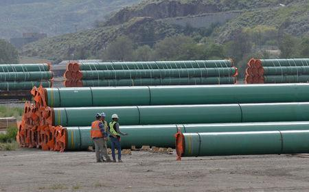 Workmen inspect steel pipe to be used in oil pipeline construction at a stockpile site in Kamloops, British Columbia