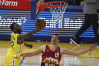Golden State Warriors' Andrew Wiggins, left, shoots against the Denver Nuggets' Nikola Jokic at an NBA basketball game in San Francisco, Friday, April 23, 2021. (AP Photo/Jed Jacobsohn)