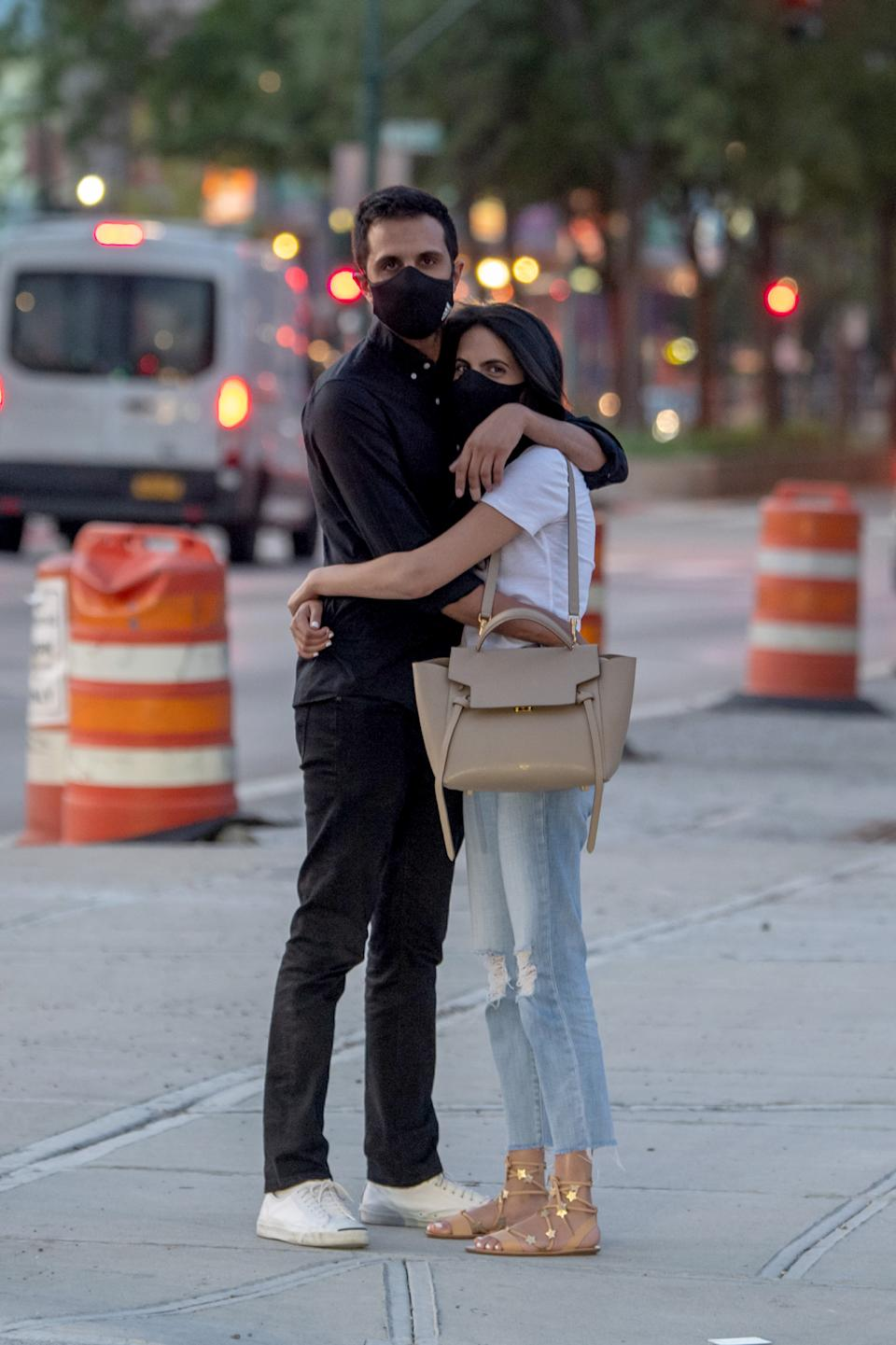 NEW YORK, NEW YORK - JULY 21: A couple wearing masks are seen hugging on the sidewalk as the city enters Phase 4 of re-opening following restrictions imposed to slow the spread of coronavirus on July 21, 2020 in New York City. The fourth phase allows outdoor arts and entertainment, sporting events without fans and media production. (Photo by Alexi Rosenfeld/Getty Images)