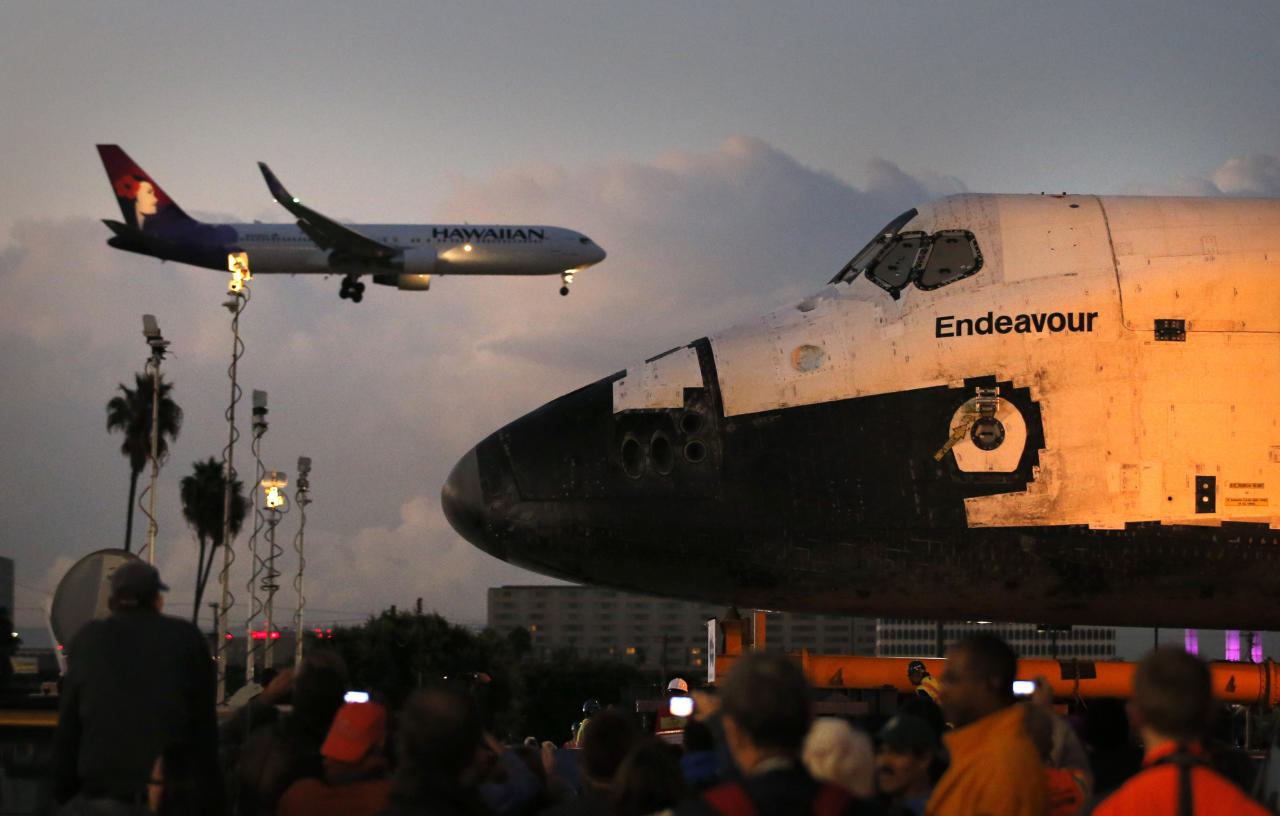 The space shuttle Endeavour sits in a strip mall as a Hawaiian Airlines jet approaches a runway at Los Angeles International Airport in Los Angeles, Friday, Oct. 12, 2012. Endeavour's 12-mile road trip kicked off shortly before midnight Thursday as it moved from its Los Angeles International Airport hangar en route to the California Science Center, its ultimate destination, said Benjamin Scheier of the center. (AP Photo/Jae C. Hong)