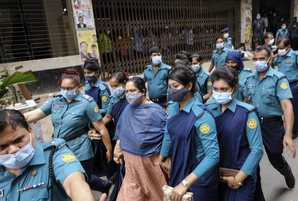 Bangladeshi journalist Rozina Islam, center, is escorted by police to a court in Dhaka, Bangladesh, Tuesday, May 18, 2021. Police in Bangladesh's capital have arrested the prominent journalist on charges of stealing and photographing sensitive state information. (AP Photo/Mahmud Hossain Opu)