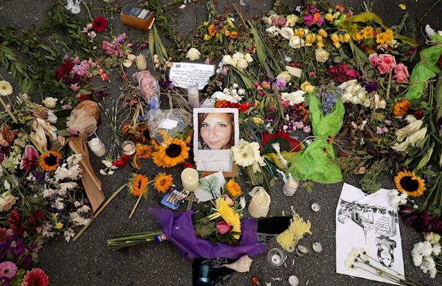<p>Flowers, candles and chalk-written messages surround a photograph of Heather Heyer on the spot where she was killed and 19 others injured when a car slamed into a crowd of people protesting against a white supremacist rally, Aug. 16, 2017 in Charlottesville, Va. (Photo: Chip Somodevilla/Getty Images) </p>