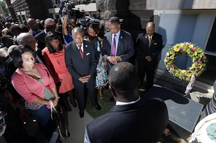 Rev. Julius Scruggs, third from left, leads people in prayer during a wreath laying ceremony at the 16th Street Baptist Church in Birmingham, Ala., Sunday, Sept. 15, 2013. The congregation gathered outside the church for the wreath laying ceremony at the spot where a bomb was detonated 50 years ago by the Ku Klux Klan, killing four young girls. Rev. Jesse Jackson is fourth from left. U.S. Rep. Terri Sewell, D-Ala., is second from left. (AP Photo/Hal Yeager)