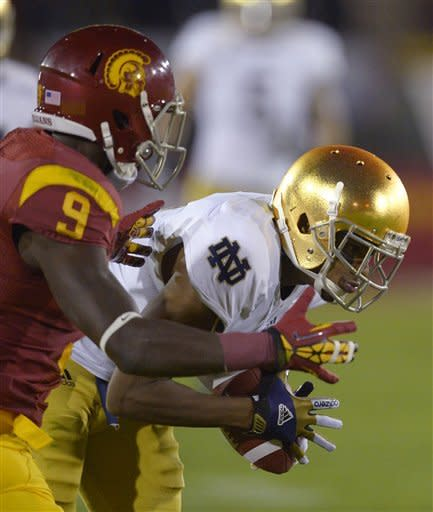 Notre Dame cornerback KeiVarae Russell, right, intercepts a pass intended for Southern California wide receiver Marqise Lee, left, during the first half of an NCAA college football game, Saturday, Nov. 24, 2012, in Los Angeles. (AP Photo/Mark J. Terrill)