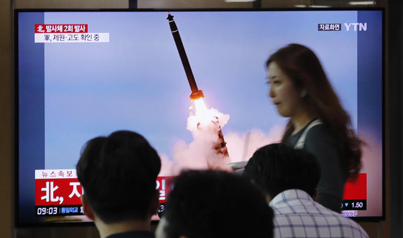 """People watch a TV showing a file image of an unspecified North Korea's missile launch during a news program at the Seoul Railway Station in Seoul, South Korea, Tuesday, Sept. 10, 2019. North Korea launched at least two unidentified projectiles toward the sea on Tuesday, South Korea's military said, hours after the North offered to resume nuclear diplomacy with the United States but warned its dealings with Washington may end without new U.S. proposals. The sign reads """" North Korea launched at least two unidentified projectiles."""" (AP Photo/Ahn Young-joon)"""