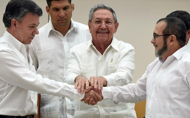 Colombian President Juan Manuel Santos (left) and FARC leader Timoleon Jimenez shake hands as Cuban President Raul Castro (centre) holds their hands during a meeting in Havana, on September 23, 2015 (AFP Photo/Luis Acosta)