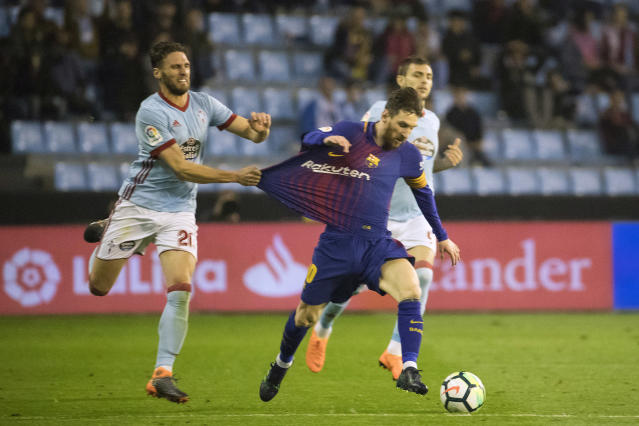Barcelona's Lionel Messi, right, challenges for the ball with RC Celta's Sergi Gmez during a Spanish La Liga soccer match between RC Celta and Barcelona at the Balaidos stadium in Vigo, Spain, Tuesday, April 17, 2018. (AP Photo/Lalo R. Villar)