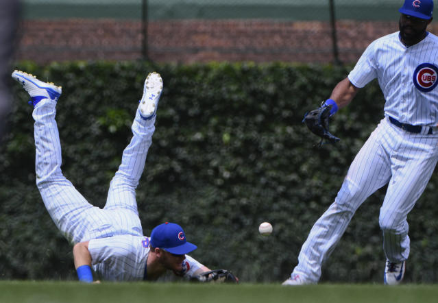 Chicago Cubs center fielder Ian Happ, left, and right fielder Jason Heyward try for the ball hit for a double by Los Angeles Dodgers' Yasiel Puig (66) during the sixth inning of a baseball game on Tuesday, June 19, 2018, in Chicago. (AP Photo/Matt Marton)