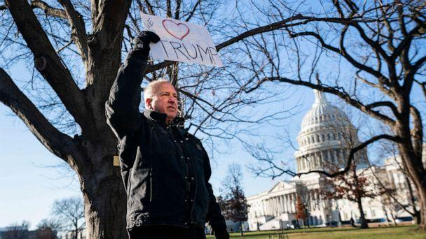 PHOTO: A lone Trump supporter holds a sign in support of the President outside the Capitol in Washington, Dec. 18, 2019. (Jim Lo Scalzo/EPA via Shutterstock)