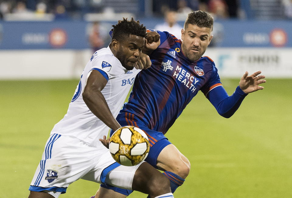Montreal Impact's Orji Okwonkwo, left, challenges FC Cincinnati's Greg Garza during the second half of an MLS soccer match Saturday, Sept. 14, 2019, in Montreal. (Graham Hughes/The Canadian Press via AP)