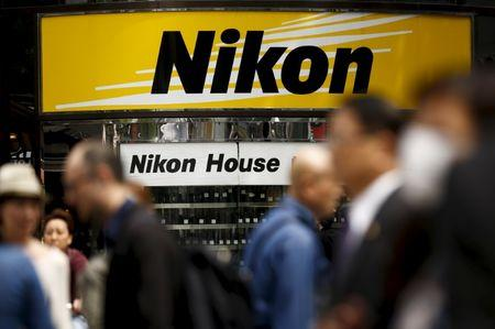 People walk past a retailer of Nikon cameras and lenses in central Tokyo