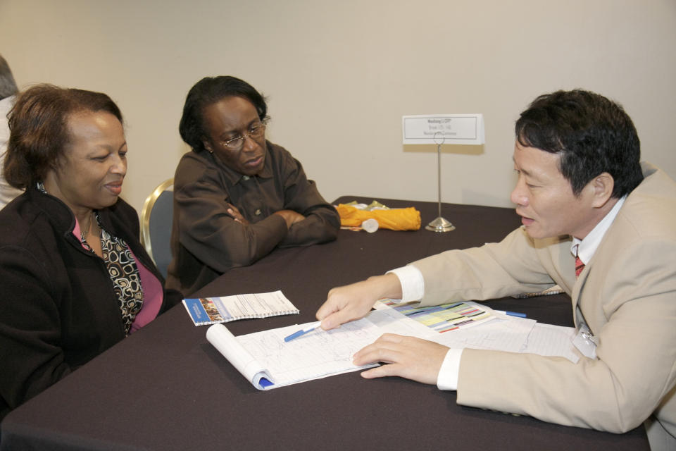 A retirement advisor talking to two women at the Free Financial Planning Clinic at Hyatt Regency Hotel. (Photo by: Jeffrey Greenberg/Universal Images Group via Getty Images)
