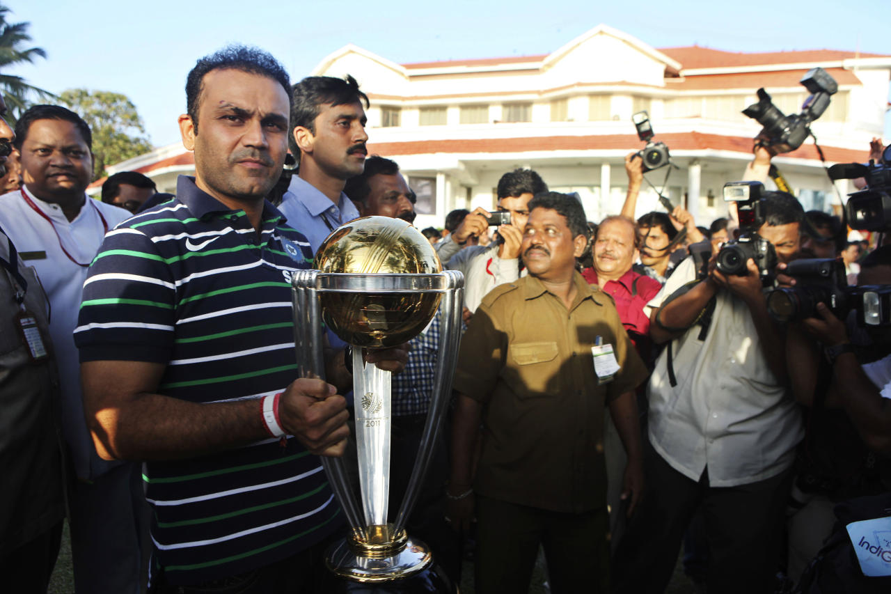 India's Virender Sehwag, left, poses with the trophy during a tea party at Maharashtra state governor's house in Mumbai, India, Sunday, April 3, 2011. Indian cricket team lifted the Cricket World Cup Saturday night for the first time in 28 years after a six-wicket victory against Sri Lanka at the Wankhede Stadium.
