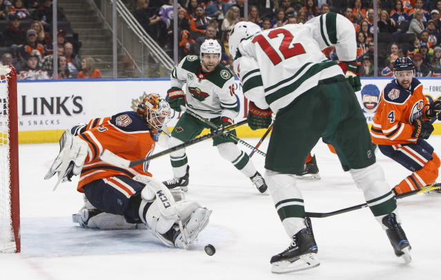 Minnesota Wild center Eric Staal (12) and Minnesota Wild left wing Jason Zucker (16) are stopped by Edmonton Oilers goaltender Cam Talbot (33) during the third in an NHL hockey game in Edmonton, Alberta, Friday, Dec. 7, 2018. (Jason Franson/The Canadian Press via AP)