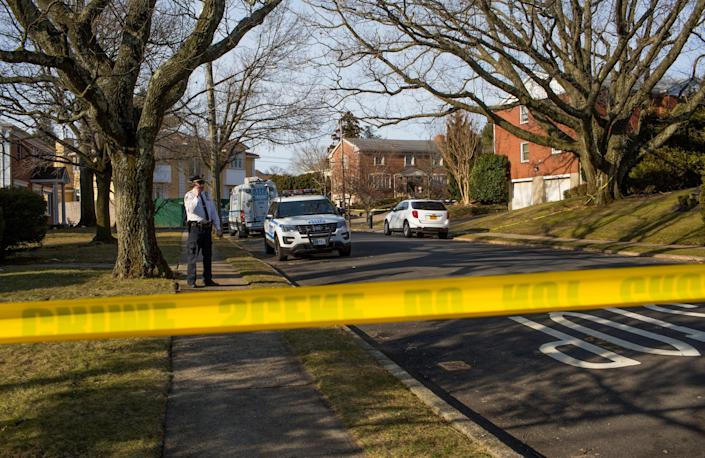 Yellow police tape is seen on a tree-lined city block with large homes.