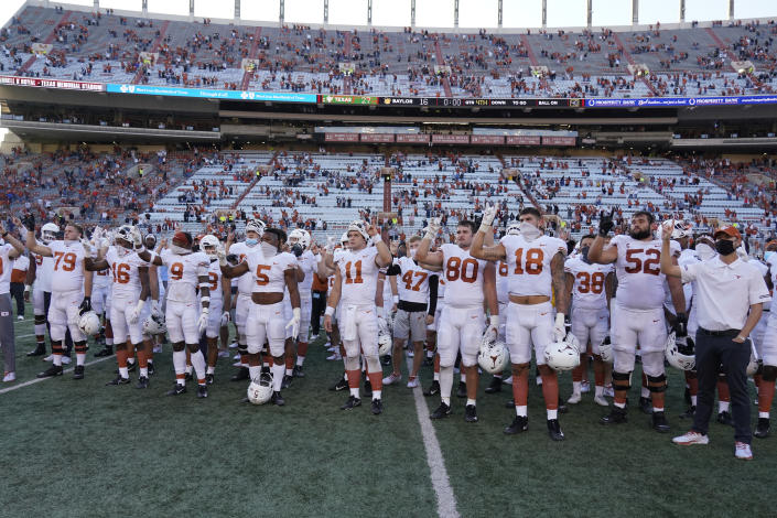 """FILE - In this Saturday, Oct. 24, 2020, file photo, Texas players, including Sam Ehlinger (11), sing """"The Eyes Of Texas"""" after an NCAA college football game against Baylor in Austin, Texas. The University of Texas' long-awaited report on the history of the school song """"The Eyes of Texas"""" found it had """"no racist intent,"""" but the school will not require athletes and band members to participate in singing or playing it at games and campus events. The song had erupted in controversy in 2020 after some members of the football team demanded the school stop playing it because of racist elements in the song's past. (AP Photo/Chuck Burton, File)"""