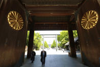 Worshippers bow at the chrysanthemum seal-bedecked gate of Yasukuni Shrine in Tokyo, Wednesday, April 21, 2021, the first day of the annual Spring Rites, the Shinto shrine's biannual festival honoring the war dead. (AP Photo/Koji Sasahara)