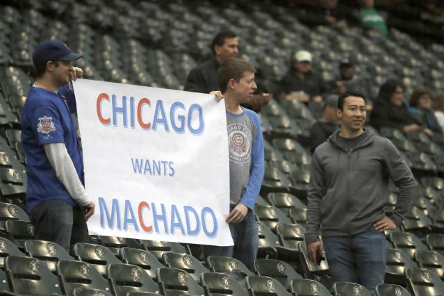Two Chicago Cubs fans hold up a sign encouraging the Cubs to go after Baltimore Orioles shortstop Manny Machado, before a baseball game between the Chicago White Sox and Orioles Monday, May 21, 2018, in Chicago. (AP Photo/Charles Rex Arbogast)