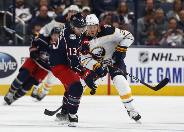 Columbus Blue Jackets forward Cam Atkinson, left, controls the puck against Buffalo Sabres forward Kyle Okposo during the first period of an NHL hockey game in Columbus, Ohio, Monday, Oct. 7, 2019. (AP Photo/Paul Vernon)
