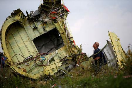 FILE PHOTO: A Malaysian air crash investigator inspects the crash site of Malaysia Airlines Flight MH17, near the village of Hrabove (Grabovo) in Donetsk region, Ukraine, July 22, 2014.  REUTERS/Maxim Zmeyev/File Photo