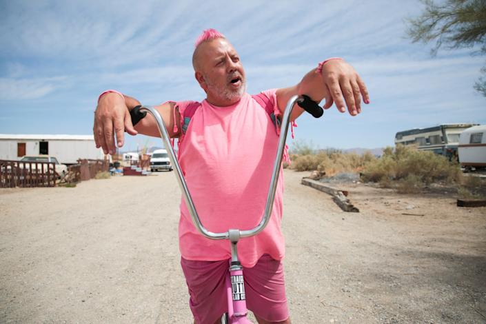 Pink Gorilla stops to chat on his bike near The Range in Slab City, Calif., on Monday, April 5, 2021. Pink Gorilla said he believes the COVID-19 pandemic is a hoax and will not get the vaccine.